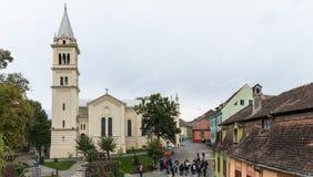 游人在正方形在罗马天主教堂附近-老城市城堡的城堡附近走  Sighisoara市在罗马尼亚 库存照片