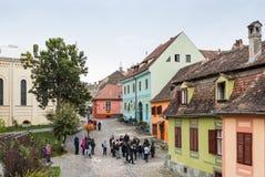 游人在正方形在罗马天主教堂附近-老城市城堡的城堡附近走  Sighisoara市在罗马尼亚 免版税库存图片