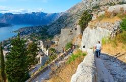 游人在步下降在科托尔,黑山的古老堡垒墙壁 免版税库存照片