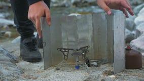 游人在河附近野营 设施手提油炉燃烧器 丙烷燃料,阵营比赛,挡风玻璃手提油炉 股票录像