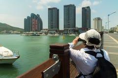 游人在海南岛上的三亚市拍摄三亚河的堤防的现代摩天大楼 库存照片