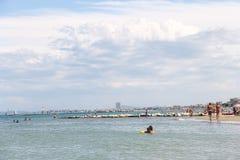 游人在海滩晒日光浴在Bellaria Igea小游艇船坞,里米尼 库存照片