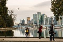游人在温哥华港口观看一架水上飞机 库存照片