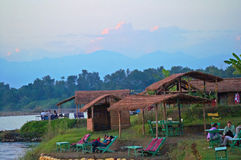 游人在狂放的河附近休息在日落期间在Chitwan国家公园,尼泊尔 免版税库存照片