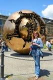 游人在球形内的球形前面站立在预言 免版税库存照片