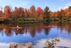 游人在秋天北卡罗来纳喜欢划皮船在湖 免版税库存图片