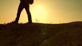 游人在美好的日落的光芒的山走 旅客的脚攀登在黄色太阳的光芒的小山 股票视频
