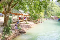 游人在蓝色盐水湖, Vangvieng,老挝享用 免版税库存图片