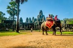 游人在象轿椅子,柬埔寨乘坐大象 免版税库存照片