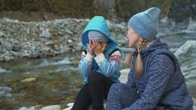 游人在远足以后休息 家庭旅行 由山,河,小河的人环境 父母和孩子走 股票视频