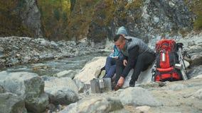 游人在远足以后休息 家庭旅行 由山,河,小河的人环境 父母和孩子走 股票录像