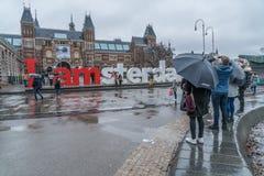 游人在雨阿姆斯特丹中 库存图片