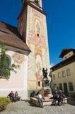 游人在马赛厄斯旁边放松Klotz雕象举世闻名的小提琴制造商在米滕瓦尔德,德国 库存图片