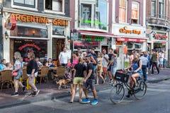 游人在寻找餐馆的阿姆斯特丹 免版税库存图片