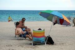 游人在Dania的一把五颜六色的沙滩伞下靠岸 库存照片