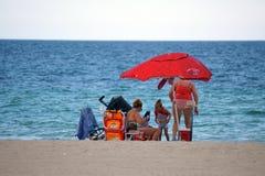 游人在Dania的一把五颜六色的沙滩伞下靠岸 库存图片