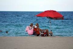 游人在Dania的一把五颜六色的沙滩伞下靠岸 免版税库存图片