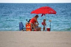 游人在Dania的一把五颜六色的沙滩伞下靠岸 免版税图库摄影