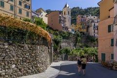 游人在Manarola,五乡地,利古里亚,意大利的历史的中心拍照片 免版税库存照片