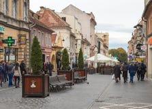 游人在Muresenilor街道走并且看视域在老镇布拉索夫在罗马尼亚 图库摄影