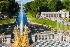 游人在Peterhof盛大小瀑布的喷泉 图库摄影
