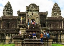 游人坐和获得乐趣在柬埔寨的吴哥窟寺庙 库存图片