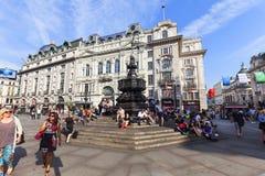 游人坐Shaftesbury纪念喷泉,皮卡迪利广场,伦敦,英国的步 库存照片