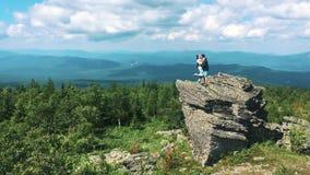 游人夫妇在山上面举行被举的手上的享用看风景地平线的自由愉快的男人和妇女  股票录像