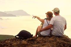 游人夫妇坐小山计划绊倒到遥远的海岛 免版税库存图片