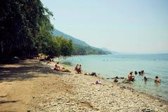 游人家庭获得在海滩的乐趣,游泳在爱琴海 库存图片