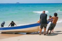 游人帮助马来西亚人有他的小船海滩 免版税库存照片