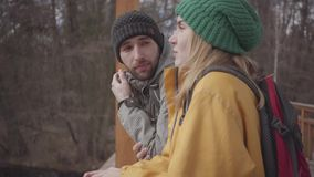 游人年轻夫妇的画象站立在有背包的桥梁的在他们的后面 有胡子的人和相当 股票录像