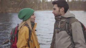 游人年轻夫妇的画象站立在有背包的河岸的在他们的后面 有胡子的人和 影视素材