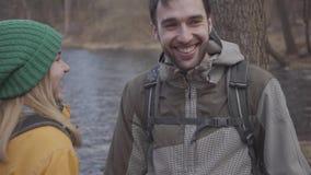 游人年轻夫妇的画象站立在有背包的河岸的在他们的后面 ?????? 影视素材