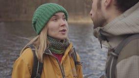 游人愉快的年轻夫妇画象站立在有背包的河岸的在他们的后面 ?????? 股票录像