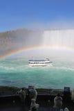 游人手表尼亚加拉瀑布在一充分的彩虹vert下的游览小船 免版税库存照片