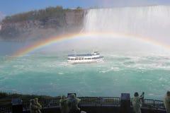 游人手表尼亚加拉瀑布在一条充分的彩虹下的游览小船 免版税库存图片