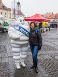 游人拍摄与在大正方形的一套米其林服装打扮的一个人在锡比乌市在罗马尼亚 免版税库存图片