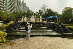 游人拍摄喷泉在入口对可敬的都市住宅复杂时间海岸在三亚市 免版税图库摄影