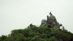 游人拍照片在岩石上面 与背包的一次旅行 猴子海岛  挑运游人 人们在 股票视频