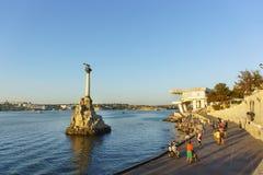游人拍照片靠近纪念碑到在塞瓦斯托波尔海湾的被破坏的船在日落 免版税库存图片