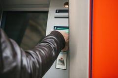 游人撤出从ATM的金钱进一步旅行的 劫掠从ATM的一张卡片 财务,信用卡,撤退 库存照片