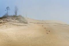 游人攀登巨大的沙丘在海角Kiwanda 免版税库存照片