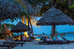 游人放松在海滩 夜间 免版税库存图片