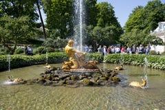 游人敬佩有氚核雕塑的温室喷泉, 免版税图库摄影