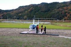 游人是下来从直升机JA002R -从Robinson Helicopter Company的鲁宾逊R44掠夺 免版税图库摄影