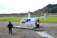游人是下来从直升机JA002R -从Robinson Helicopter Company的鲁宾逊R44掠夺 免版税库存照片