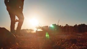 游人是啤酒开会的人由在自然野营的剪影阳光日落的篝火党运载一个轴和一个背包 影视素材