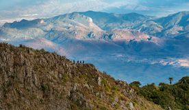 游人是在峭壁和山背景 绿色fo 免版税图库摄影