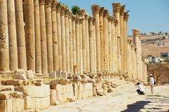 游人柱廊街道的参观废墟在古老罗马市Gerasa现代杰拉什在约旦 图库摄影